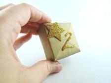 Dann noch ein bisschen Deko und die Nummerierung. Fertig. Die Kästchen könnt ihr nun einfach in einer hübschen Schale arrangieren. Oder ihr schneidet einen Strohalm klein und klebt kurze Stücke davon mit Klebestreifen auf die Rückseite der Schachtel. Da könnt ihr prima eine Schnur durchfädeln und den Adventkalender so aufhängen. Viel Spaß!